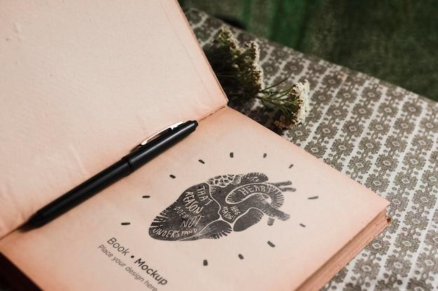 Hoge hoek van boek met bloemen en pen