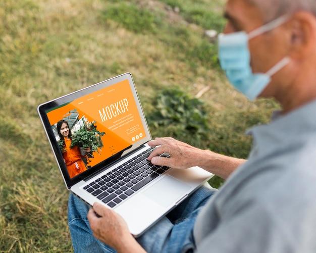 Hoge hoek van de mens op laptop in park
