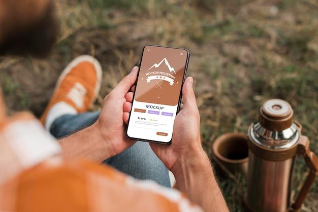 Hoge hoek van man met smartphone tijdens het kamperen