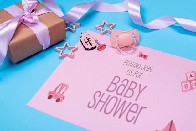 Hoge hoek van roze babyuitnodiging met cadeau