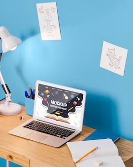 Hoge hoek van schoolbank met lamp en laptop
