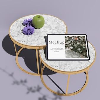 Hoge hoek van tablet op tabletten met appel en bloemen