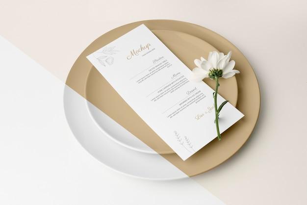 Hoge hoek van tafelopstelling met lentebloem en menumodel
