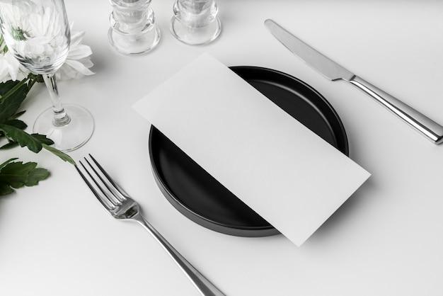 Hoge hoek van tafelopstelling met mock-up van het lentemenu en bestek