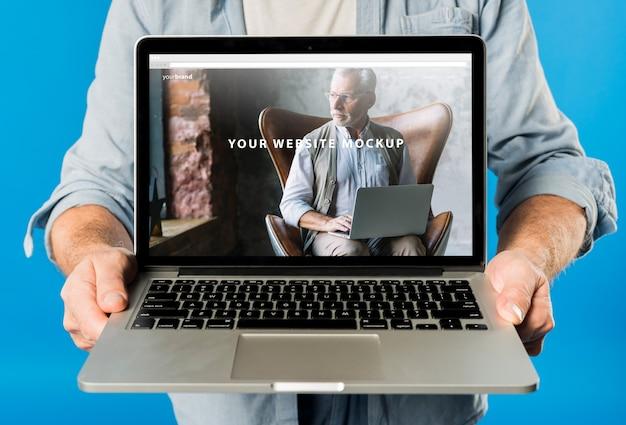 Hogere mens die laptop model voorstelt