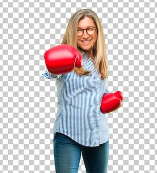 Hogere mooie vrouw die bokshandschoenen draagt