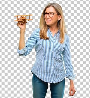 Hogere mooie vrouw met een houten vliegtuig