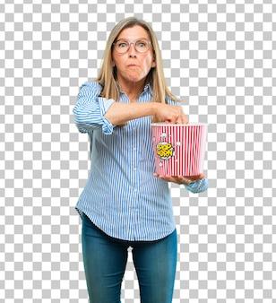 Hogere mooie vrouw met een popcornemmer
