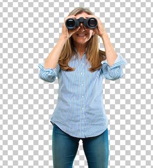 Hogere mooie vrouw met verrekijkers