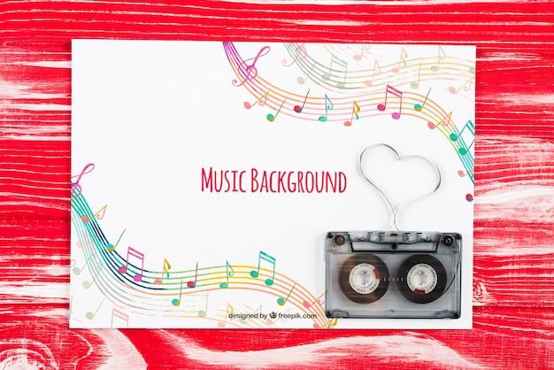 Hoja con notas musicales y cinta al lado