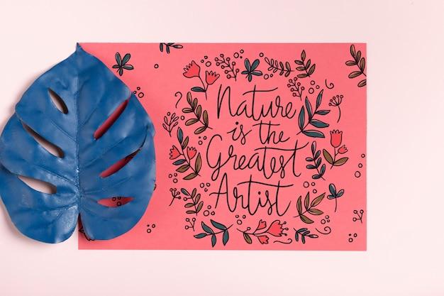 Hoja pintada realista al lado de papel con mensaje