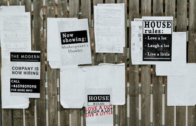 Hojas de anuncios de papel en una valla de madera.