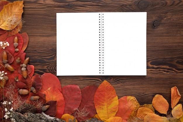 Hojas de otoño, galletas y cuaderno de papel.