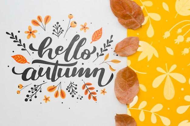 Hola letras de otoño junto al patrón de hojas amarillas