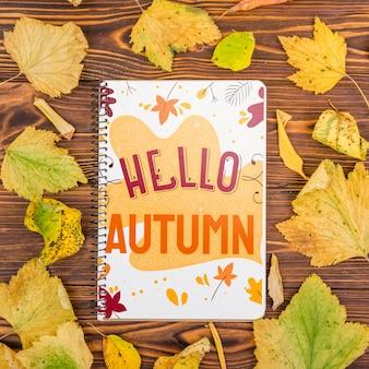 Hola mensaje de otoño en el cuaderno con maqueta