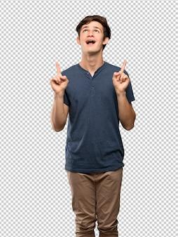 Hombre adolescente sorprendido y apuntando hacia arriba