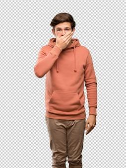 Hombre adolescente con sudadera que cubre la boca con las manos por decir algo inapropiado