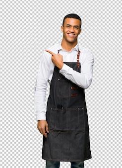 Hombre afroamericano joven barbero apuntando al lado para presentar un producto