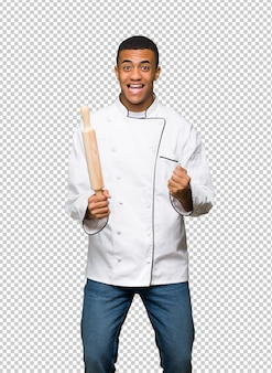 Hombre afroamericano joven del cocinero que celebra una victoria en la posición del ganador