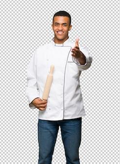 Hombre afroamericano joven del cocinero que sacude las manos para cerrar un buen trato