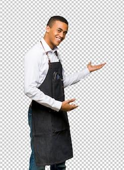 Hombre afroamericano joven del peluquero que señala detrás y que presenta un producto