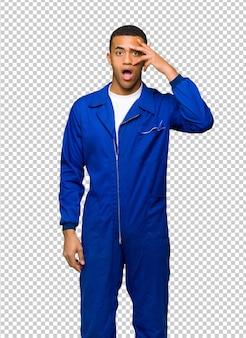 Hombre afroamericano joven del trabajador con sorpresa y expresión facial chocada