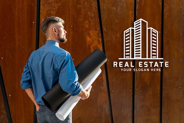 Hombre agente sosteniendo planes para nuevo edificio desde atrás