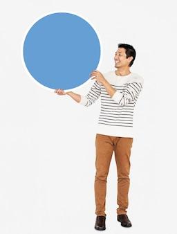 Hombre alegre sosteniendo un círculo azul en blanco