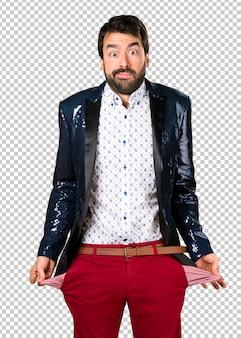 Hombre arruinado con chaqueta buscando dinero en sus bolsillos.