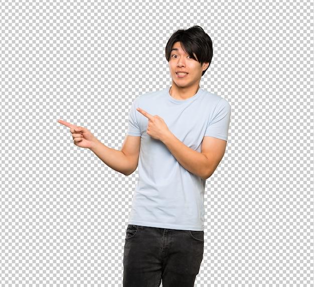 Hombre asiático con camisa azul asustado y apuntando hacia el lado.