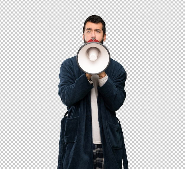 Hombre con barba en pijama gritando a través de un megáfono