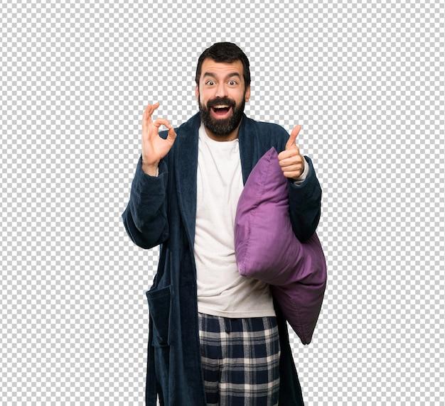 Hombre con barba en pijama que muestra signo y pulgar bien arriba gesto