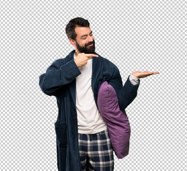 Hombre con barba en pijama sosteniendo copyspace imaginario en la palma para insertar un anuncio