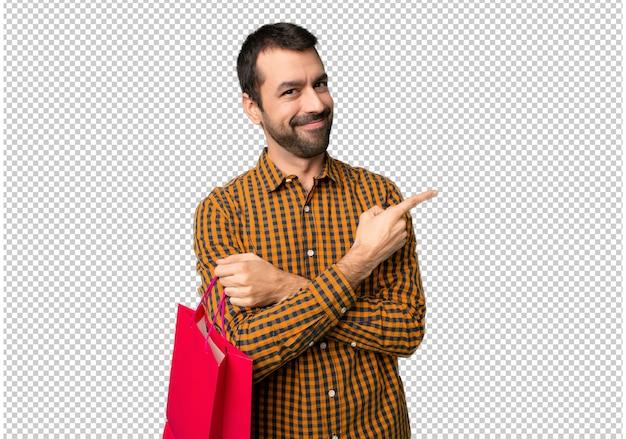 Hombre con bolsas de compra apuntando al costado para presentar un producto.