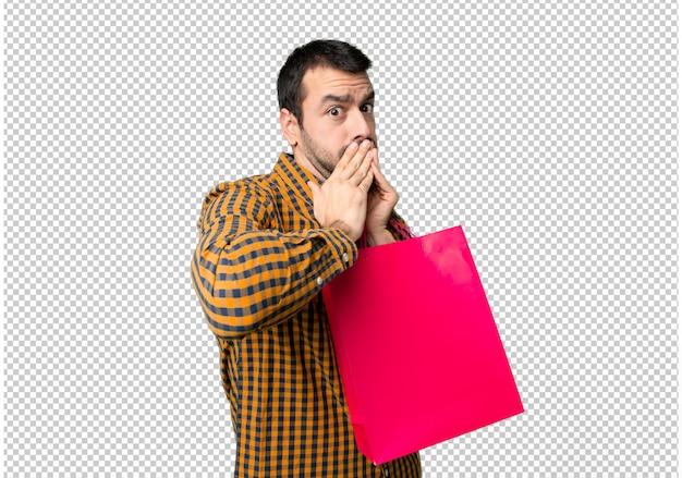 Hombre con bolsas de compra cubriéndose la boca con las manos por decir algo inapropiado.