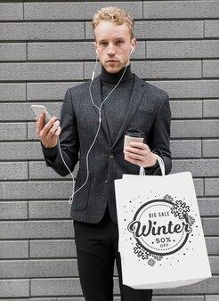Hombre con bolsas de compras y sosteniendo móvil