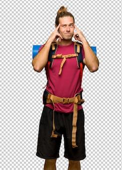 Hombre caminante con mochilero de montaña teniendo dudas y pensando