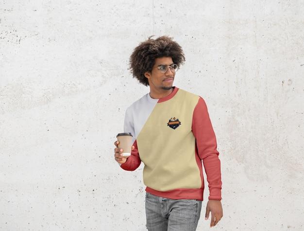 Hombre con capucha tomando café