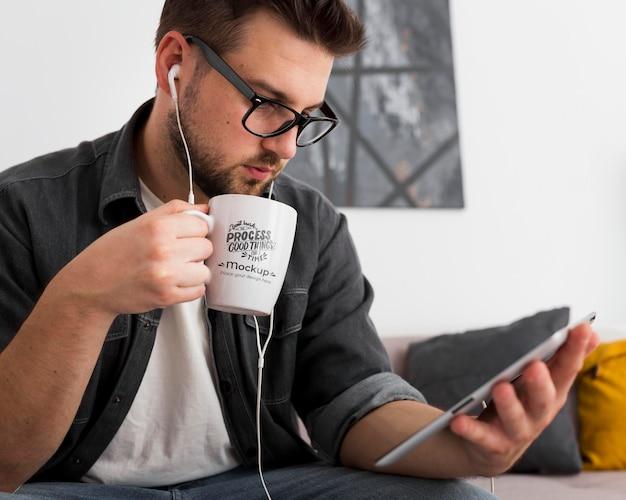 Hombre en casa bebiendo de maqueta de taza