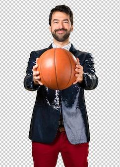 Hombre con chaqueta sosteniendo una pelota de basket