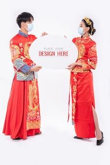 Hombre chino y mujer china sostienen maqueta de bocadillo en blanco
