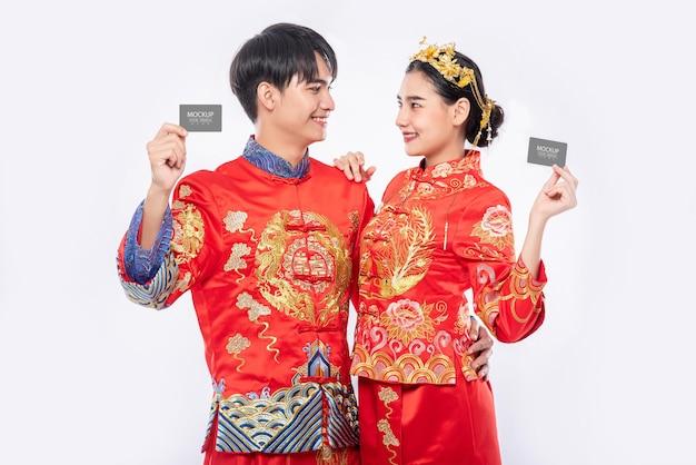 Hombre chino y mujer china tienen maqueta de tarjeta de crédito en blanco