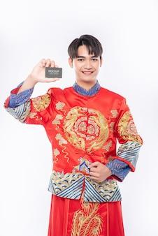 Hombre chino sostiene maqueta de tarjeta de crédito en blanco