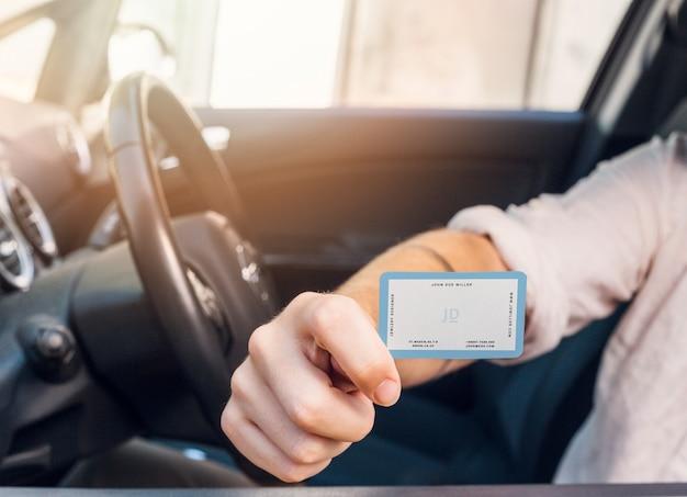 Hombre en coche con mockup de tarjeta de visita