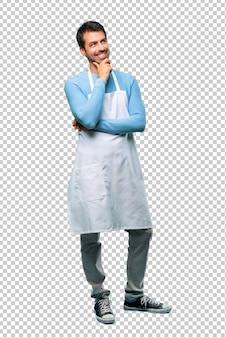 Hombre con un delantal de pie y pensando en una idea.