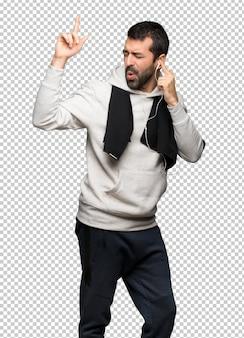 Hombre del deporte escuchando música con auriculares y bailando.
