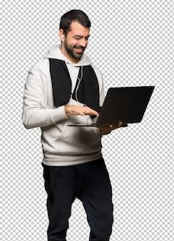 Hombre deportivo con laptop y celebrando una victoria.