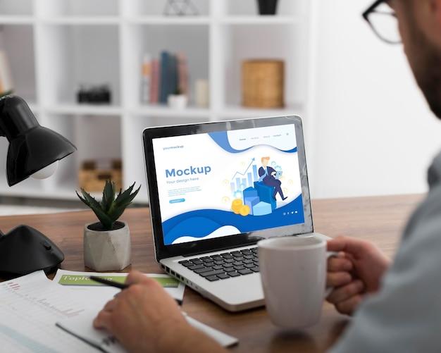 Hombre en escritorio con maqueta de portátil
