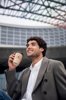 Hombre en espacios limpios urbanos modernos con maqueta de taza