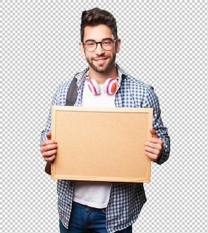 Hombre estudiante sosteniendo un panel de corcho